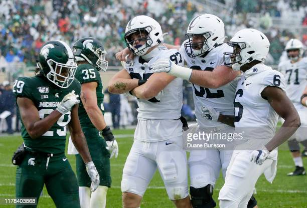 Tight end Pat Freiermuth celebrates his touchdown with Michal Menet and Justin Shorter of the Penn State Nittany Lions as Shakur Brown and Joe Bachie...