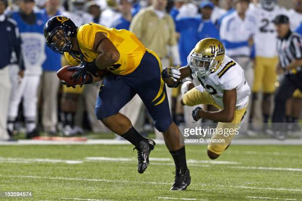 Tight end Richard Rodgers of the California Golden Bears catches a pass and breaks a tackle from cornerback Sheldon Price of the UCLA Bruins during...