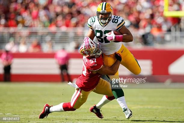 Tight end Richard Rodgers of the Green Bay Packers is tackled by inside linebacker Michael Wilhoite of the San Francisco 49ers during their NFL game...