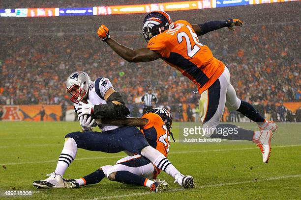 Tight end Rob Gronkowski of the New England Patriots is tackled by free safety Bradley Roby of the Denver Broncos and hit by free safety Darian...