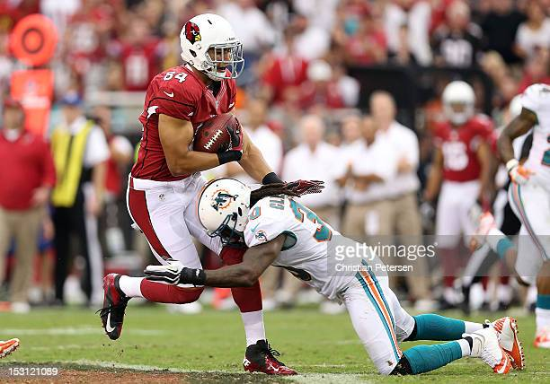 Tight end Rob Housler of the Arizona Cardinals is tackled by strong safety Chris Clemons of the Miami Dolphins after a reception during the NFL game...