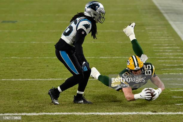 Tight end Robert Tonyan of the Green Bay Packers dives for a first down over the defense of cornerback Donte Jackson of the Carolina Panthers during...
