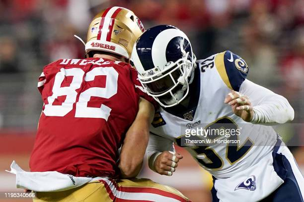 Tight end Ross Dwelley of the San Francisco 49ers catch a pass for a first down and free safety Eric Weddle of the Los Angeles Rams is penalized for...