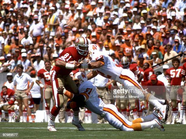 Tight End Russ Francis of the San Francisco 49ers catches a pass and is immediately pounced on by Line Backers Chris Washington and Scot Brantley of...