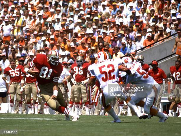 Tight End Russ Francis of the San Francisco 49ers caught a pass for yardage and will be tackled by Line Backers Chris Washington and Scot Brantley of...