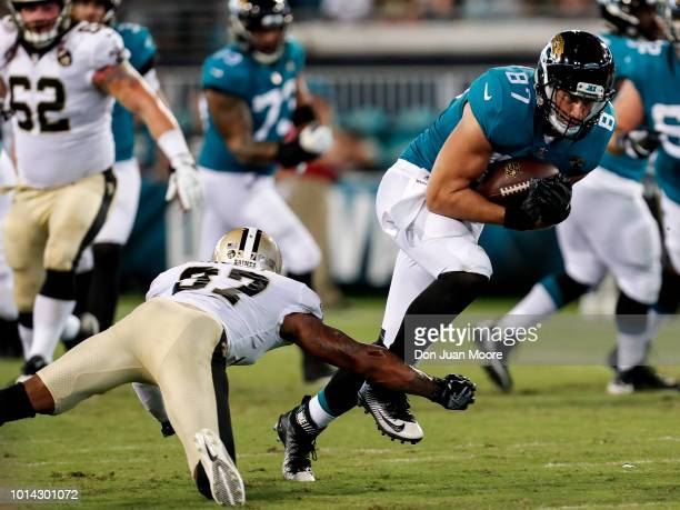 Tight End Scott Orndoff of the Jacksonville Jaguars avoids a tackle by Cornerback Dee Delaney of the New Orleans Saints during a preseason game at...