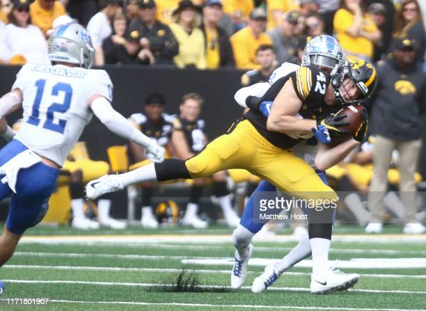 Tight end Shaun Beyer of the Iowa Hawkeyes makes a catch during the first half in front of cornerback Justin Brown of the Middle Tennessee Blue...