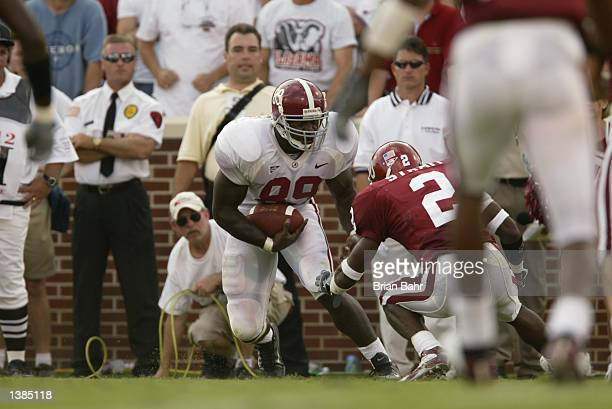 Tight end Theo Sanders of the Alabama Crimson Tide battles for extra yardage past defensive back Derrick Strait of the Oklahoma Sooners during the...