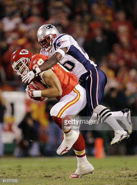 Tight end Tony Gonzalez of the Kansas City Chiefs catches the ball wrapped up by defensive back Eugene Wilson of the New England Patriots in...