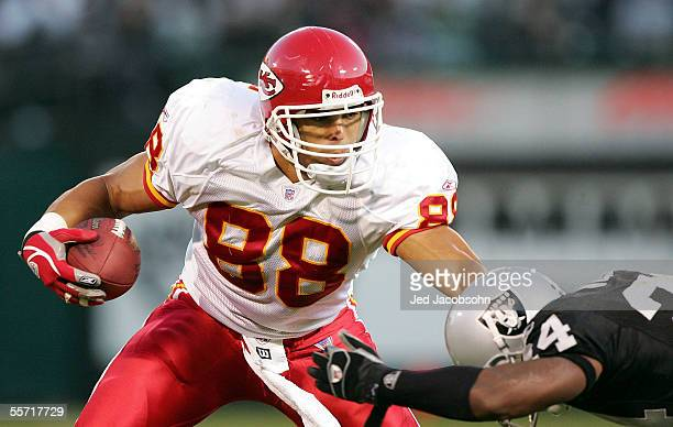 Tight end Tony Gonzalez of the Kansas City Chiefs looks to avoid a tackle by cornerback Charles Woodson of the Oakland Raiders at McAfee Coliseum on...