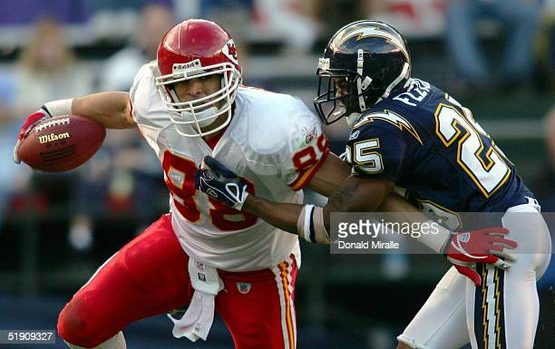 Tight end Tony Gonzalez of the Kansas City Chiefs runs with the ball against the tackle of defensive back Jamar Fletcher of the San Diego Chargers at...