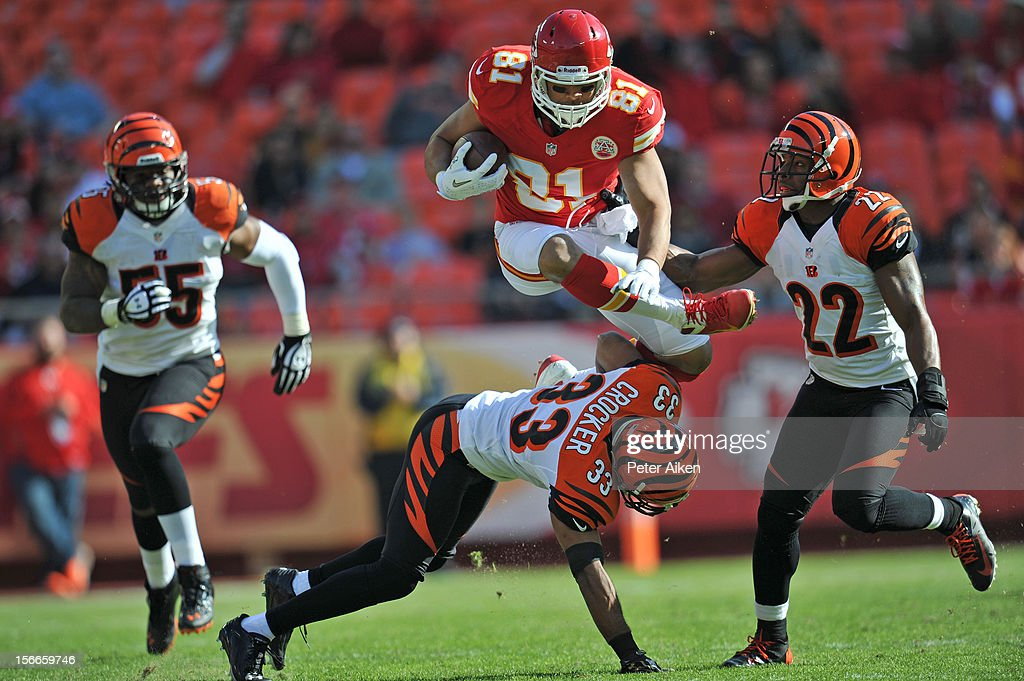 Tight end Tony Moeaki #81 of the of the Kansas City Chiefs leaps over defenders Chris Crocker #33 and Nate Clements #22 of the Cincinnati Bengals in route to a first down during the first half on November 18, 2012 at Arrowhead Stadium in Kansas City, Missouri.