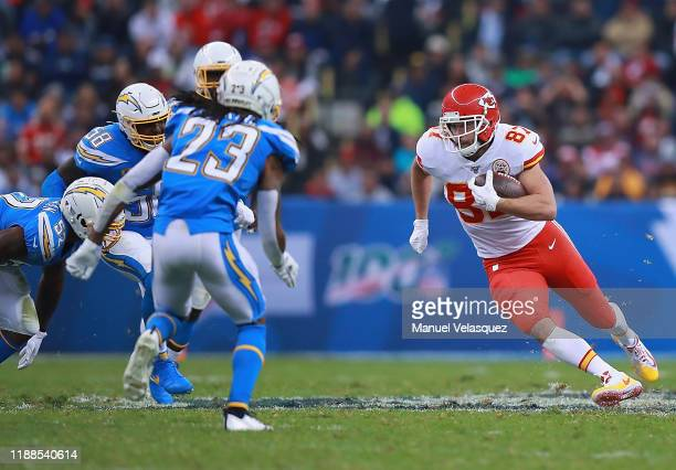 Tight end Travis Kelce of the Kansas City Chiefs carries the ball against the defense of the Los Angeles Chargers during the game at Estadio Azteca...