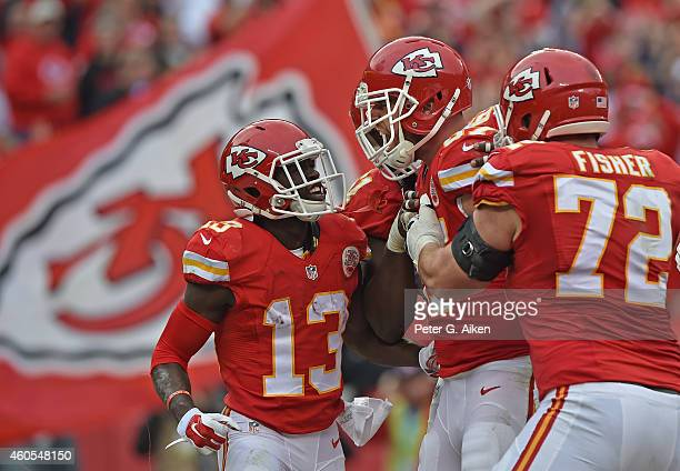 Tight end Travis Kelce of the Kansas City Chiefs celebrates with teammates De'Anthony Thomas and Eric Fisher after scoring a touchdown against the...
