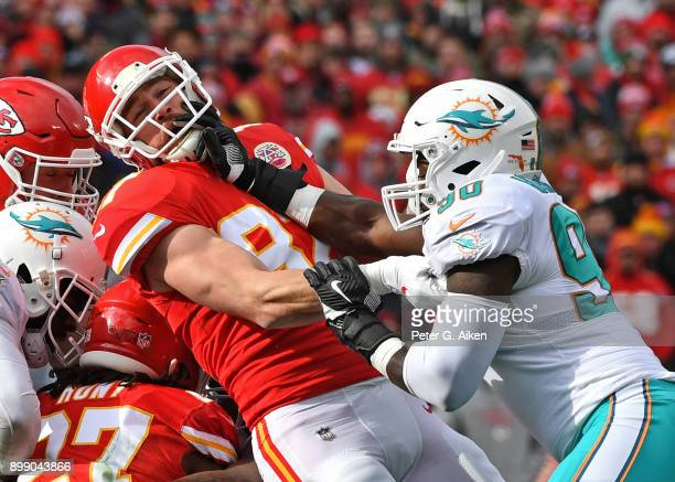 Tight end Travis Kelce of the Kansas City Chiefs gets blocked by defensive end Charles Harris of the Miami Dolphins during the first half of the game...
