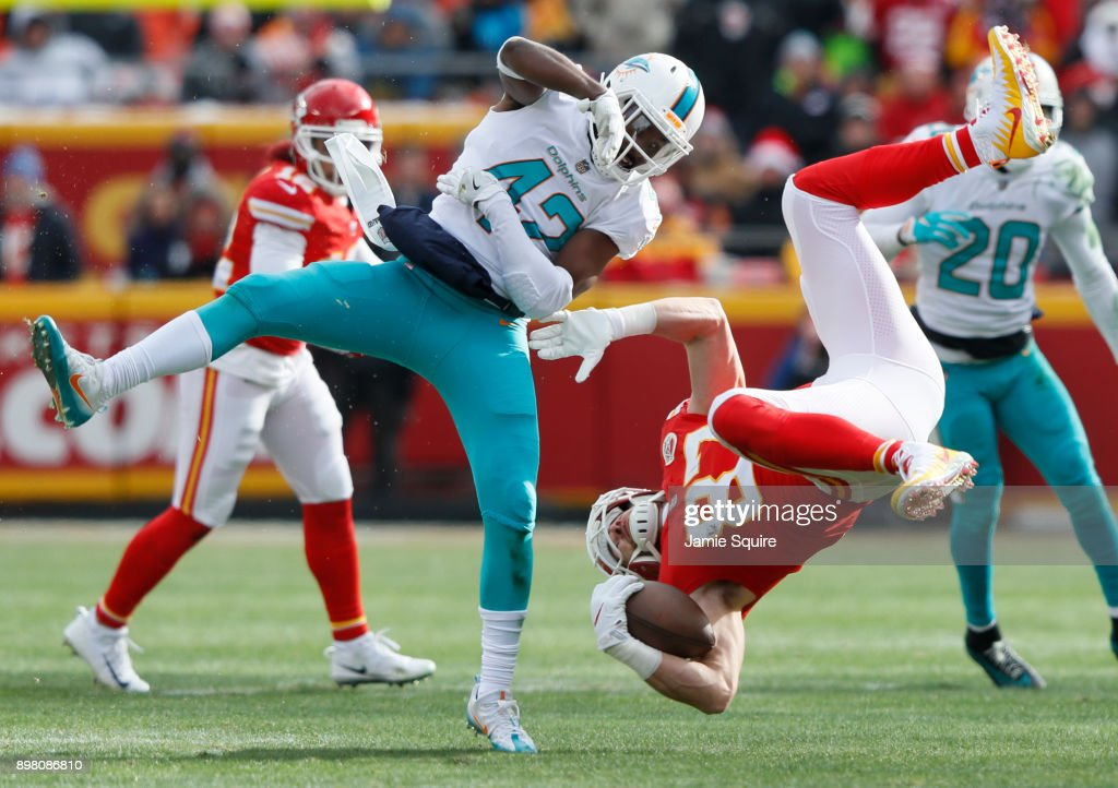 Tight end Travis Kelce #87 of the Kansas City Chiefs gets flipped upside down after leaving his feet on a tackle by defensive back Alterraun Verner #42 of the Miami Dolphins during the second quarter of the game at Arrowhead Stadium on December 24, 2017 in Kansas City, Missouri.