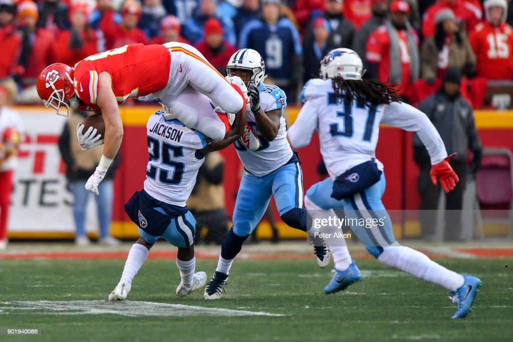 Tight end Travis Kelce #87 of the Kansas City Chiefs goes up in the air while being tackled by cornerback Adoree' Jackson #25 of the Tennessee Titans during the first quarter of the AFC Wild Card playoff game at Arrowhead Stadium on January 6, 2018 in Kansas City, Missouri.