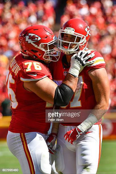 Tight end Travis Kelce of the Kansas City Chiefs is congratulated by teammate Laurent DuvernayTardif after his amazing catch during the game tying...