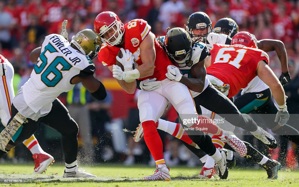 Tight end Travis Kelce #87 of the Kansas City Chiefs is tackled by defensive end Dante Fowler #56 of the Jacksonville Jaguars and teammate Johnathan Cyprien #37 at Arrowhead Stadium during the second quarter of the game on November 6, 2016 in Kansas City, Missouri.