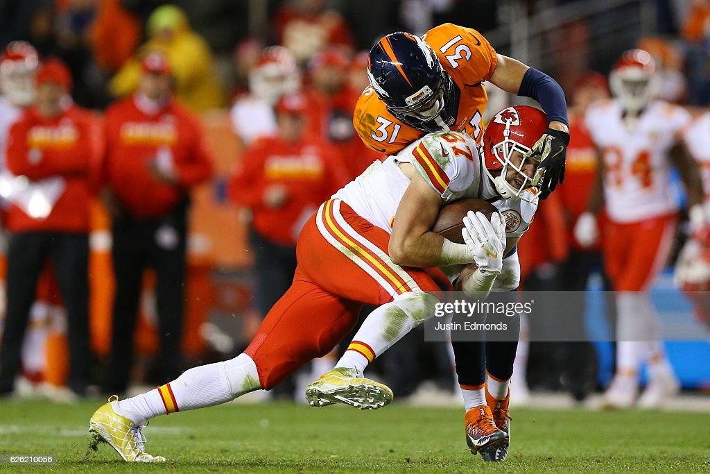 Tight end Travis Kelce #87 of the Kansas City Chiefs is tackled by free safety Justin Simmons #31 of the Denver Broncos after catching a pass in overtime at Sports Authority Field at Mile High on November 27, 2016 in Denver, Colorado.