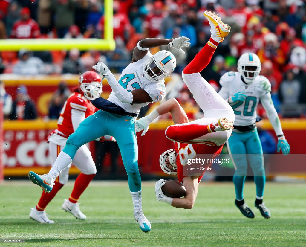 Tight end Travis Kelce #87 of the Kansas City Chiefs is upended by defensive back Alterraun Verner #42 of the Miami Dolphins after making a catch during the 1st half of the game at Arrowhead Stadium on December 24, 2017 in Kansas City, Missouri.