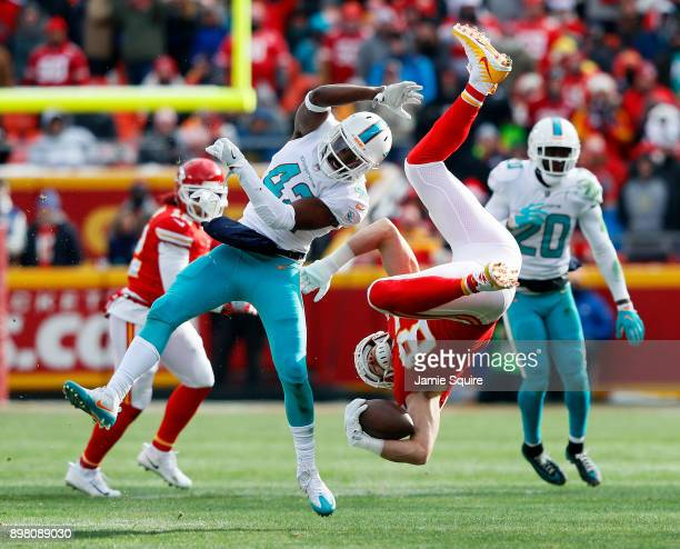 Tight end Travis Kelce of the Kansas City Chiefs is upended by defensive back Alterraun Verner of the Miami Dolphins after making a catch during the...