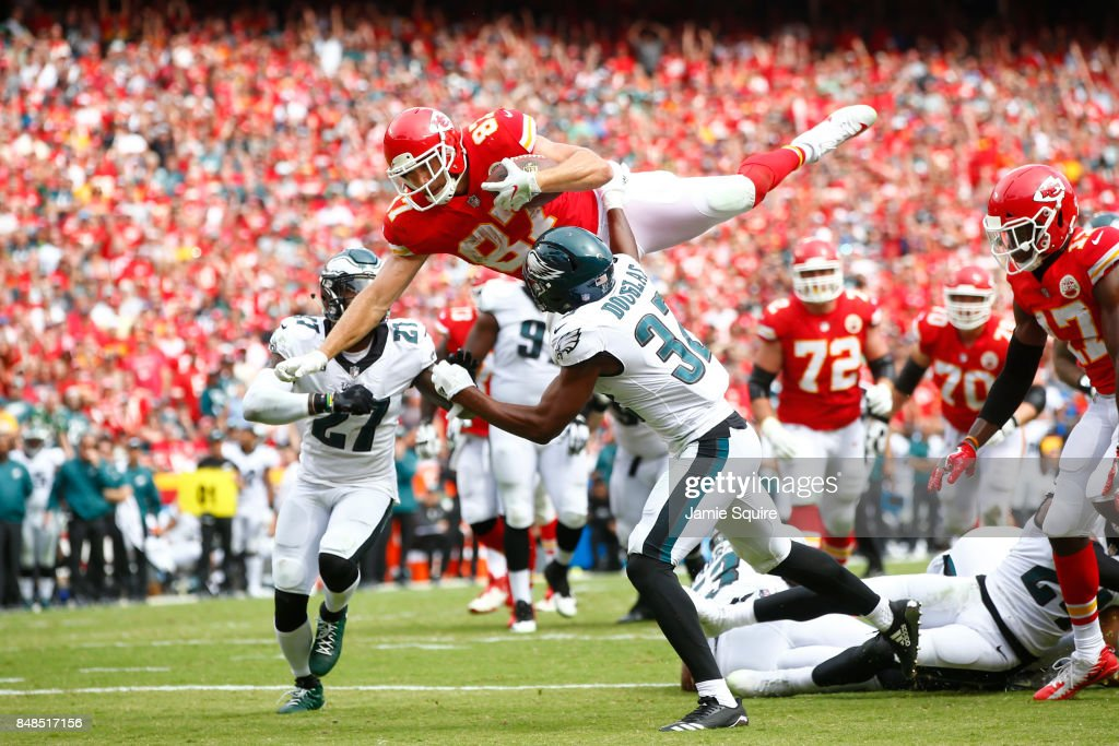 Tight end Travis Kelce #87 of the Kansas City Chiefs leaps into the end zone over Philadelphia Eagles tacklers in the fourth quarter of the game between the at Arrowhead Stadium on September 17, 2017 in Kansas City, Missouri.