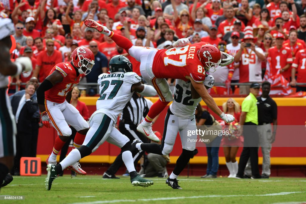 Tight end Travis Kelce #87 of the Kansas City Chiefs leaps into the end zone over Malcolm Jenkins #27 and Rasul Douglas #32 of the Philadelphia Eagles in the fourth quarter of the game at Arrowhead Stadium on September 17, 2017 in Kansas City, Missouri.
