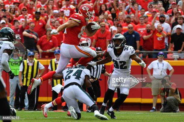 Tight end Travis Kelce of the Kansas City Chiefs leaps into the end zone over Corey Graham and Rasul Douglas of the Philadelphia Eagles in the fourth...
