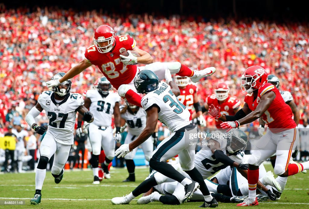 Tight end Travis Kelce #87 of the Kansas City Chiefs leaps over defenders into the end zone for a touchdown during the 2nd half of the game against the Philadelphia Eagles at Arrowhead Stadium on September 17, 2017 in Kansas City, Missouri.