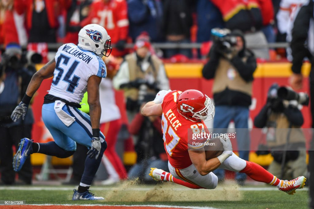 Tight end Travis Kelce #87 of the Kansas City Chiefs loses his footing while making a touchdown catch in front of inside linebacker Avery Williamson #54 of the Tennessee Titans during the first quarter of the AFC Wild Card playoff game at Arrowhead Stadium on January 6, 2018 in Kansas City, Missouri.