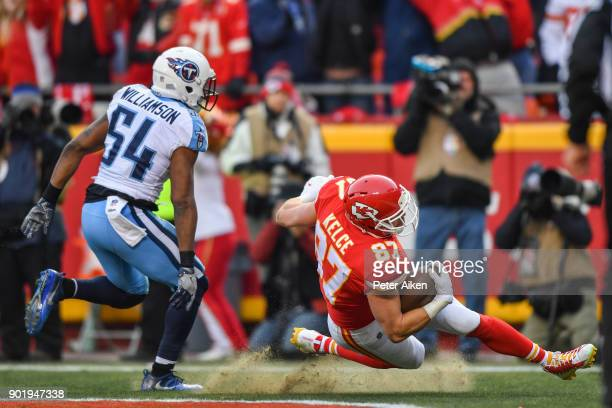 Tight end Travis Kelce of the Kansas City Chiefs loses his footing while making a touchdown catch in front of inside linebacker Avery Williamson of...