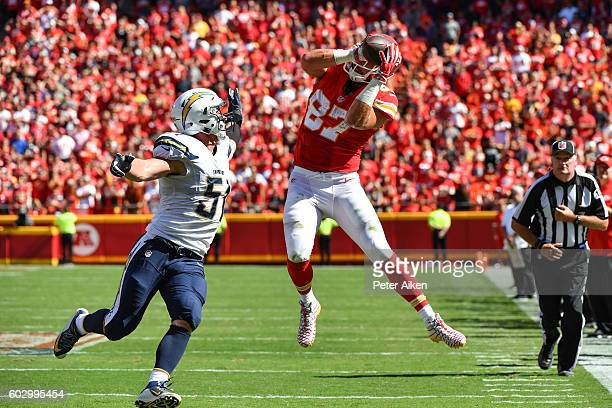Tight end Travis Kelce of the Kansas City Chiefs makes an amazing leaping catch over the outstretched arm of outside linebacker Kyle Emanuel of the...