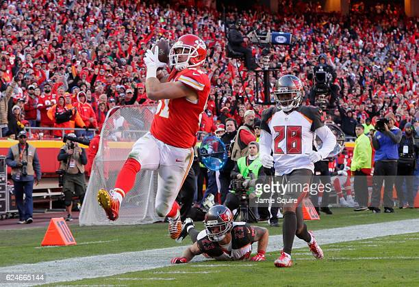 Tight end Travis Kelce of the Kansas City Chiefs tries to high step away from would be tackler strong safety Chris Conte of the Tampa Bay Buccaneers...