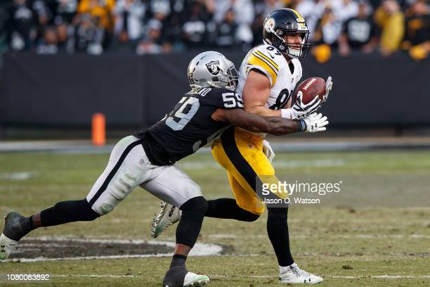 Tight end Vance McDonald of the Pittsburgh Steelers catches a pass in front of linebacker Tahir Whitehead of the Oakland Raiders during the third...