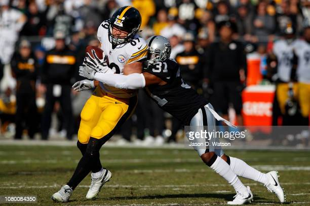 Tight end Vance McDonald of the Pittsburgh Steelers is tackled by safety Marcus Gilchrist of the Oakland Raiders during the second quarter at the...