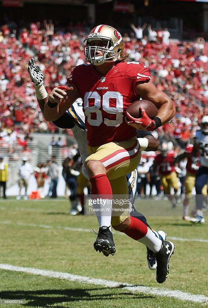 Tight end Vance McDonald #89 of the San Francisco 49ers scores a touchdown beating Darrell Stuckey #25 of the San Diego Chargers to the goal line during the second quarter of the preseason game at Levi's Stadium on August 24, 2014 in Santa Clara, California.