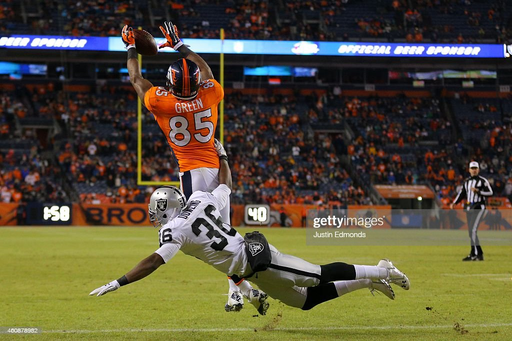Tight end Virgil Green #85 of the Denver Broncos has a 1-yard fourth quarter touchdown reception under coverage by defensive back Ras-I Dowling #36 of the Oakland Raiders at Sports Authority Field at Mile High on December 28, 2014 in Denver, Colorado.