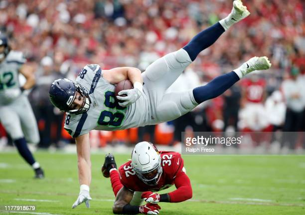 Tight end Will Dissly of the Seattle Seahawks is up-ended by safety Budda Baker of the Arizona Cardinals after a catch during the first half of the...