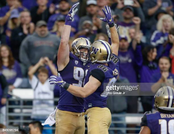 Tight end Will Dissly of the Washington Huskies is congratulated by tight end Jacob Kizer after scoring a touchdown against the Montana Grizzlies at...