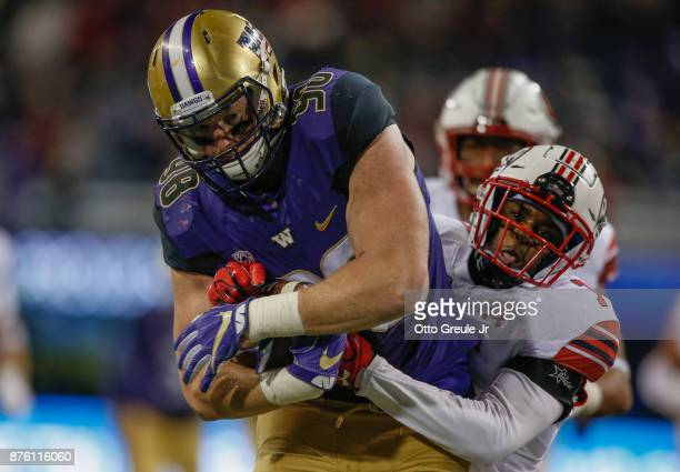 Tight end Will Dissly of the Washington Huskies rushes for a first down to the two yard line in the fourth quarter against defensive back Jaylon...
