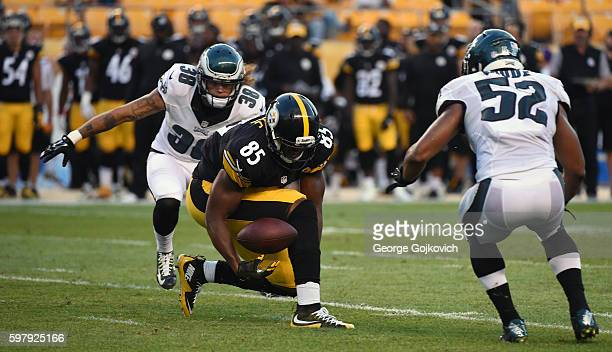 Tight end Xavier Grimble of the Pittsburgh Steelers juggles the football and is unable to catch a pass as cornerback Aaron Grymes and linebacker...