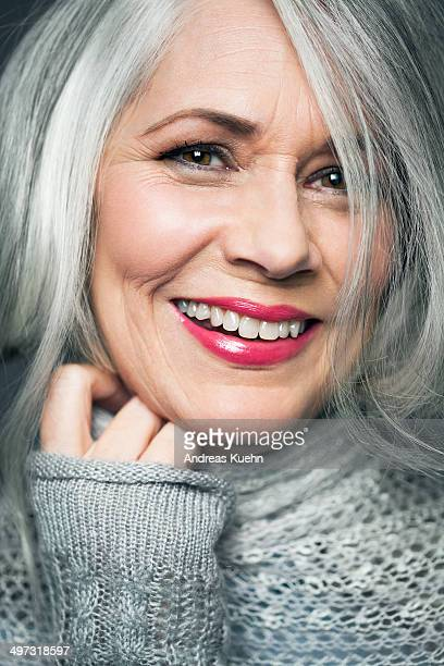 Tight portrait of grey haired lady with red lips.