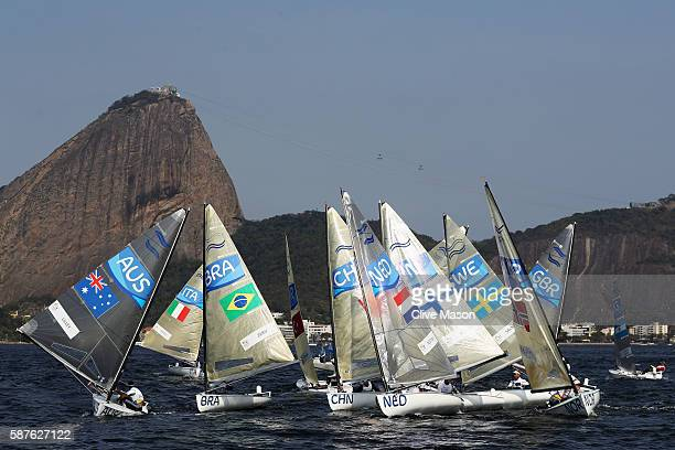 Tight racing in the Finn class race with Sugar Loaf Mountain in the background on Day 4 of the Rio 2016 Olympic Games at the Marina da Gloria on...