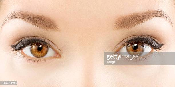 tight shot of models eyes and eye makeup - eye liner stock photos and pictures