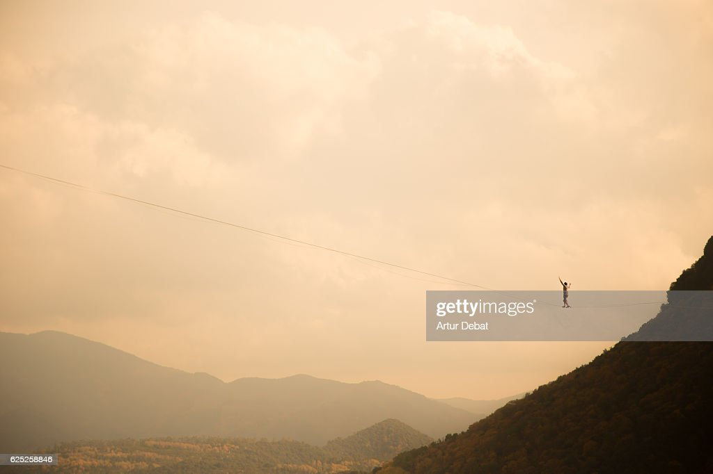 Tightrope walker in a stunning outdoor nature walking between two cliffs over the nature with nice sky. : Stock Photo