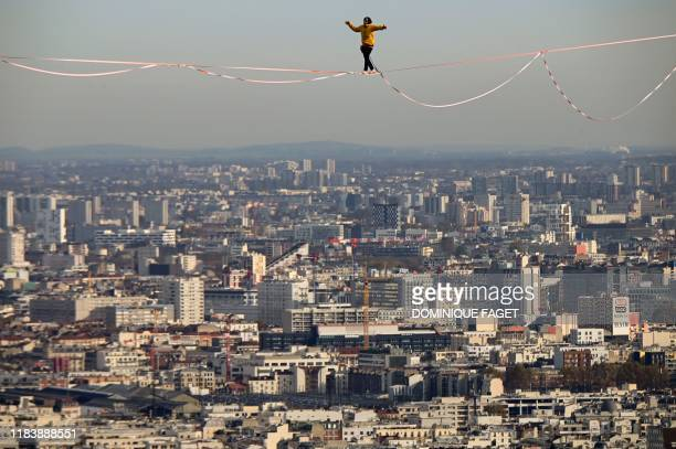 A tightrope walker performs at 150 meters high over the business district of La Defense on the outskirts of Paris on November 22 2019 as part of a...