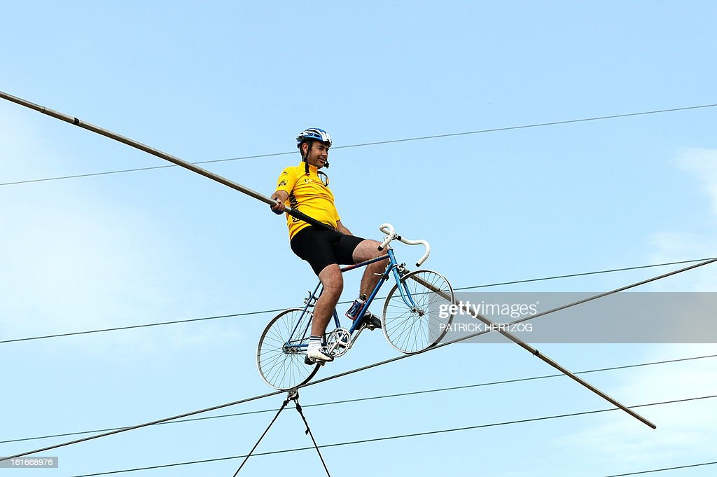 A tightrope walker, wearing a yellow jersey, performs, on July 27 ...