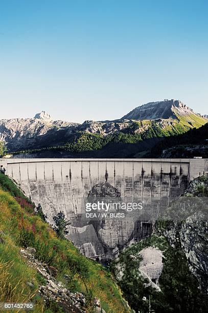 Tignes dam on Chevril lake, with the The Giant of Tignes mural in the centre of the dam by Jean Marie Pierret , Rhone-Alpes, France.