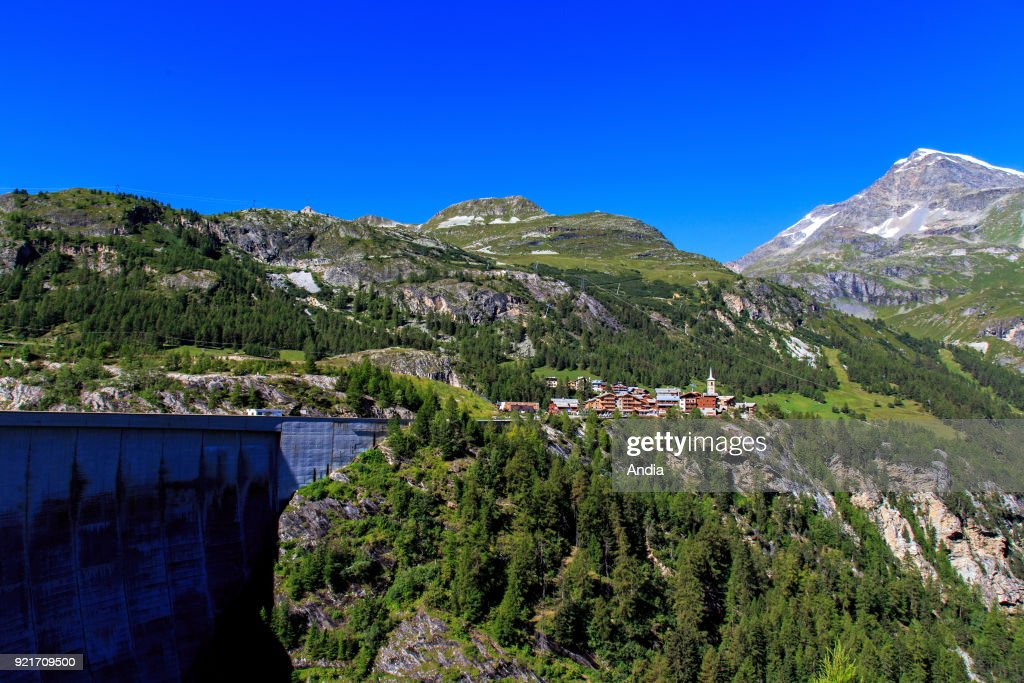 the village and the ski resort of Tignes in summer with the dam of the reservoir of 'lac du Chevril' lake.